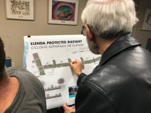 Person places dot on Elenda Street board
